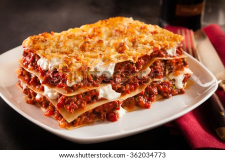 Serving of spicy traditional Italian beef lasagne in a restaurant on a modern white square plate with a red napkin, dark counter background - stock photo