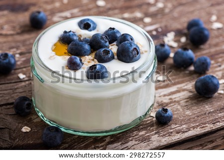 Serving of Yogurt with Whole Fresh Blueberries and Oatmeal on Old Rustic Wooden Table. Closeup Detail. - stock photo