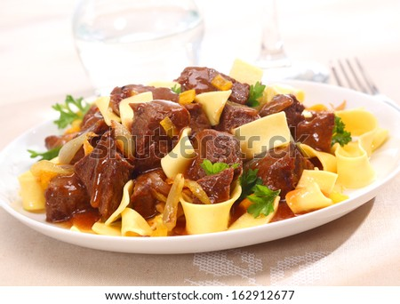 Serving on a plate of beef goulash, a stew that originated in Hungary, served with noodles and garnished with fresh chopped parsley - stock photo