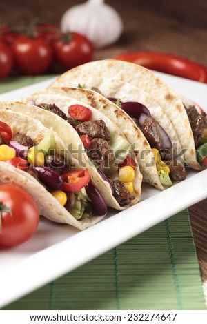 Serving taco with beef and vegetables - stock photo