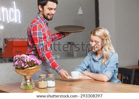 Serving to you. Young handsome waiter giving cup of coffee to pretty blond-haired woman. - stock photo