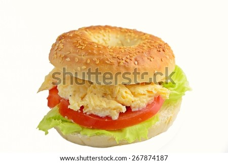 Sesame bagel with scrambled eggs, tomato and lettuce. Studio isolated - stock photo
