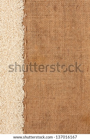 Sesame lying on sackcloth space for text - stock photo
