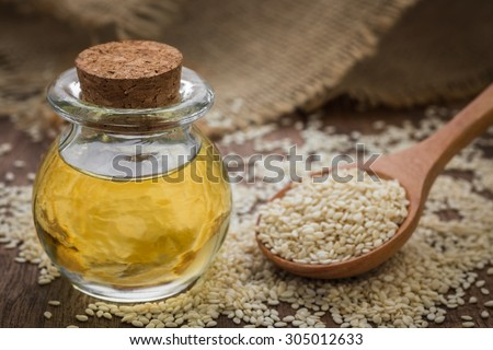 Sesame oil in glass jar and sesame seeds on wooden spoon - stock photo