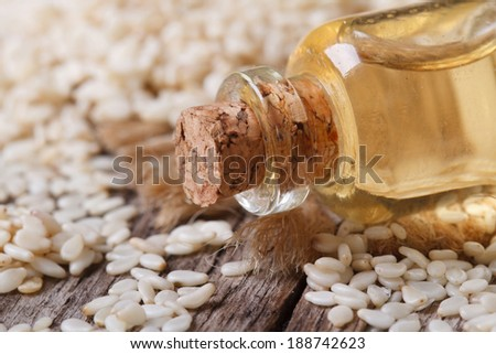 sesame seed oil in a glass bottle with a cork on the table macro horizontal  - stock photo