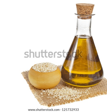 Sesame seeds and glass oil isolated on white background - stock photo