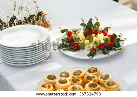 Set a variety of meat, fish and fruit snacks on a table at the restaurant to celebrate the solemn event. Background food. - stock photo