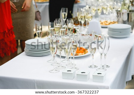 Set a variety of meat, fish and fruit snacks on a table with wine glasses  outdoors to celebrate the solemn event. Catering business. - stock photo