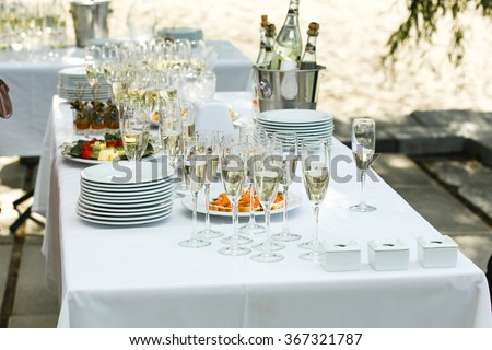 Set a variety of sweets, wine glasses and fruit snacks on a table outdoors to celebrate the solemn event. Catering business. - stock photo