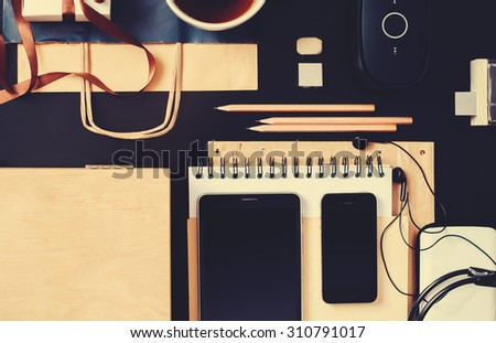 Set for Business Men with Black and Beige Accessories on office wooden table. Devices Phone, Tablet, Earphones. Top view toned - stock photo