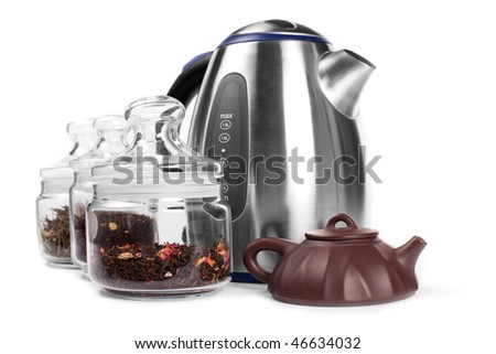 Set for drinking tea: tea in containers, metal kettle, yixing clay teapot  isolated on white. - stock photo