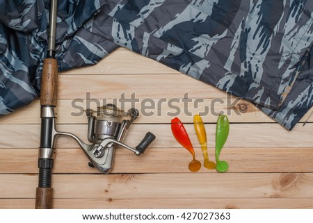 Set for fishing on the wooden background with camouflage clothing. Coil, colored rubber bait, spinning, fishing rod. Fishing and recreation. - stock photo