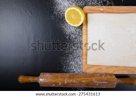 Set for home baking on a black background with flour. Rolling pin, dough, half of lemon. - stock photo