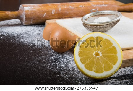 Set for home baking on a black background with flour. Rolling pin, dough, half of lemon, baking form, eggshell. - stock photo