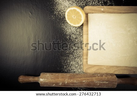 Set for home baking on a black background with flour. Rolling pin, dough, half of lemon. Toned. - stock photo