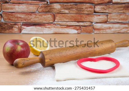 Set for home baking on a light wooden table with flour. Rolling pin, baking form, dough, half of lemon, apple. - stock photo