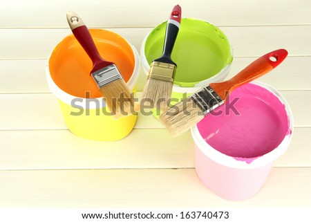 Set for painting: paint pots, brushes on white wooden table - stock photo