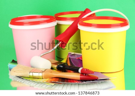 Set for painting: paint pots, brushes, paint-roller, palette of colors on green background - stock photo