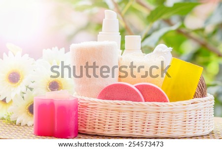 Set for spa in wicker basket, isolated on green backgrounds. - stock photo