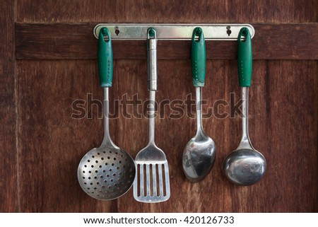 Set metal ladle and a kitchen cooking kitchen ladles on a wooden wall . - stock photo