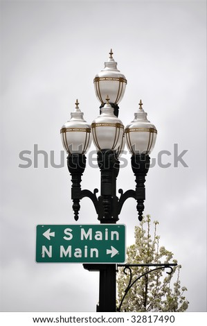 set of antique appearance street lights trimmed in gold and lampposts with directional sign of south and north main - stock photo