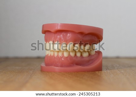 Set of artificial lower and upper jaw false teeth viewed low angle across a wooden table with copy space - stock photo