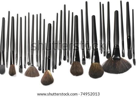 Set of black make-up brushes in row on white background. - stock photo