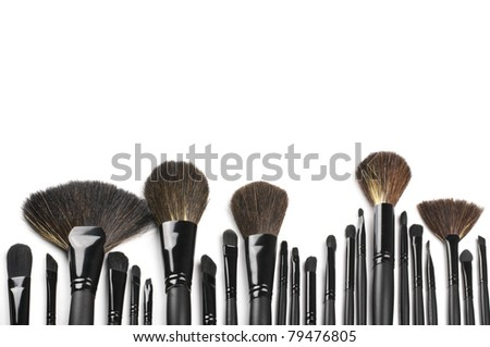 Set of black make-up brushes in row on white background as border. - stock photo