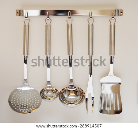 Set of black modern kitchen utensil hanging on beige background - stock photo