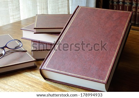 set of books set on the table, with window and library background - stock photo