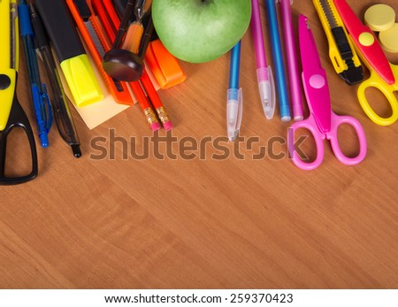 Set of bright office tools, hourglass and apple on a table - stock photo