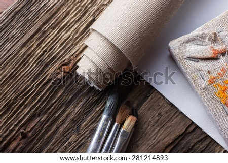 Set of brushes for painting, canvas, stapler, staples, subframe and blank white paper on old grunge natural wooden shabby desk background in painter studio. Top view - stock photo