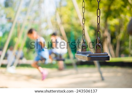 Set of chain swings on modern kids playground, kids swinging on back - stock photo