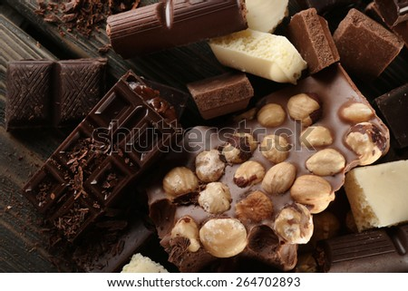 Set of chocolate with hazelnut on wooden table, closeup - stock photo