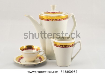 Set of coffee. White porcelain with gold maroon pattern. The coffee pot, milk jug and cup and saucer. - stock photo