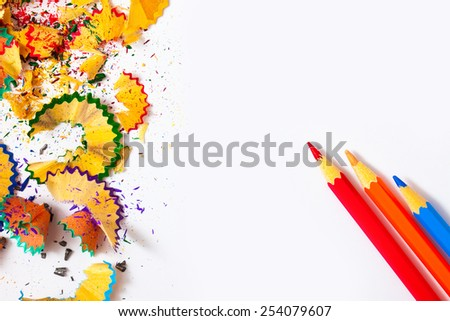 set of colored pencils and shavings on white background with copy space. - stock photo