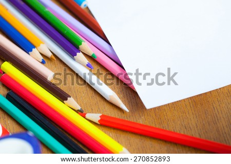 set of colored pencils with white paper. shallow depth sharpness - stock photo