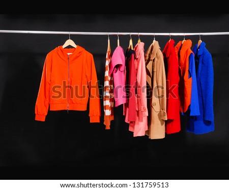 Set of colorful jacket, coat hanging on hanger-black background - stock photo