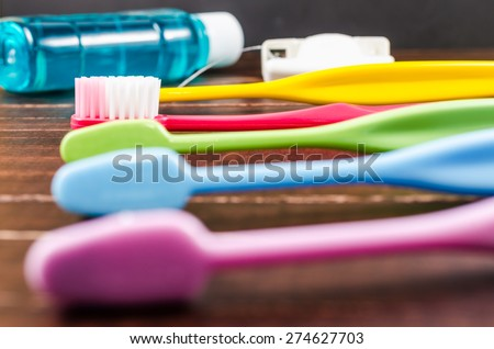 Set of colorful toothbrushs with mountwash and dental floss on wooden board - stock photo