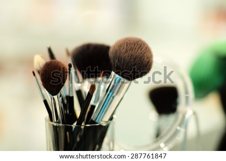 Set of cosmetic brushes in glass on light background, horizontal picture  - stock photo