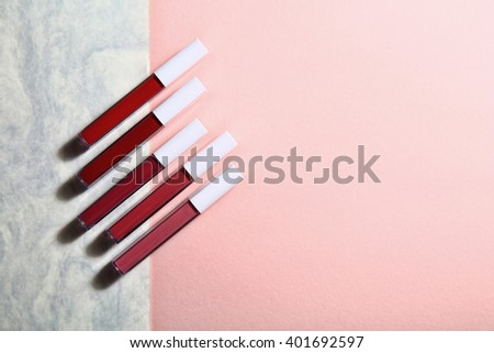 Set of cosmetics/lip gloss on light colorful background with copy-space  - stock photo