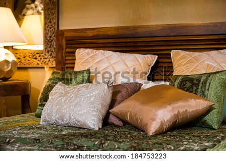 Set of cushions on the bed - stock photo