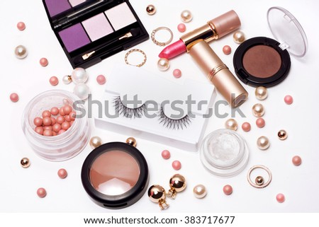Set of decorative cosmetics false eyelashes, powder, lipstick ,eye shadow white background. Top view of essentials for modern young woman. - stock photo