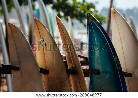 Set of different color surf boards in a stack by ocean.WELIGAMA, SRI LANKA. Surf boards on sandy Weligama beach.  On Weligama beach surf is available all year around for beginner and advanced. - stock photo