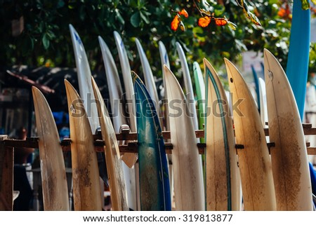 Set of different color surf boards in a stack by ocean. WELIGAMA. Surf boards on sandy Weligama beach in Sri Lanka. On Weligama beach surf is available all year around for beginner and advanced. - stock photo