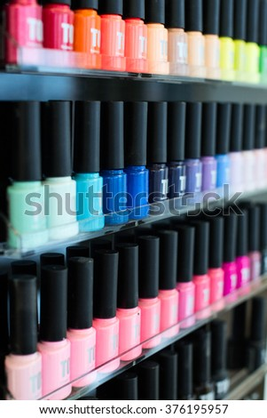 Set of different nail varnishes on shelves in cosmetic store. - stock photo