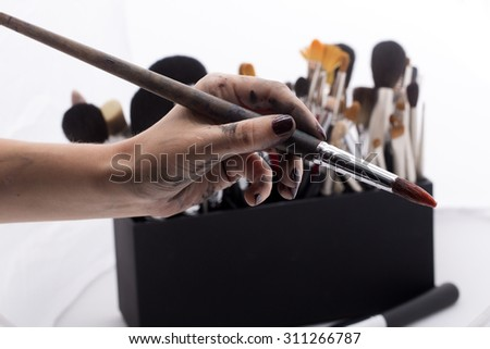 Set of different professional make-up brushes for eyeshadow powder and facial foundation for visagistes in black plastic box and human hand holding one brush on white background, horizontal picture - stock photo