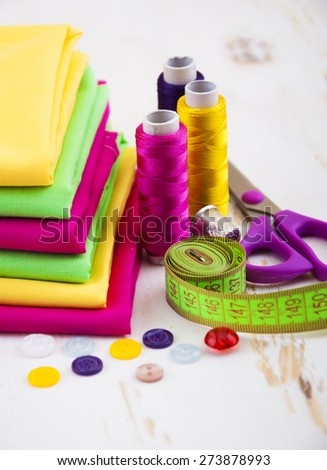 Set of different sewing accessories, fabrics and thread spools - stock photo