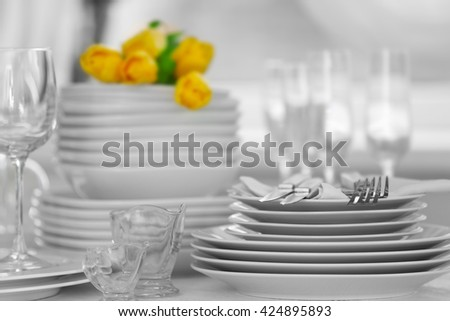 Set of dishes with yellow tulips for dinner party - stock photo