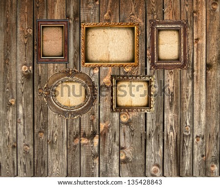 Set of empty picture frames on wooden wall - stock photo
